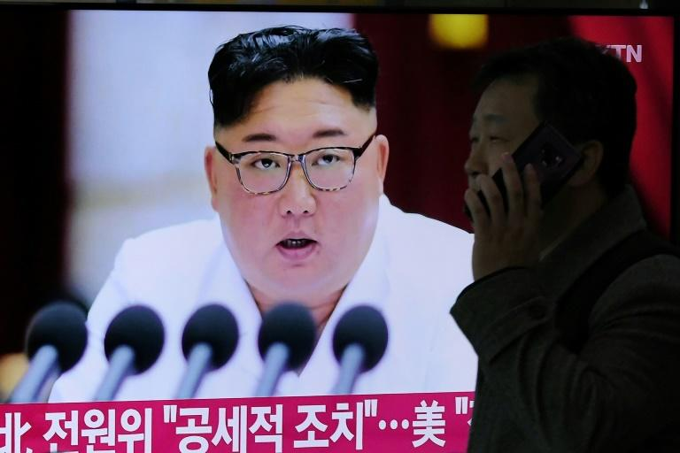 The US alleges that the regime of North Korean leader Kim Jong Un -- seen here on a television screen in December 2019 -- reaps the salary benefits of its overseas workers (AFP Photo/Jung Yeon-je)