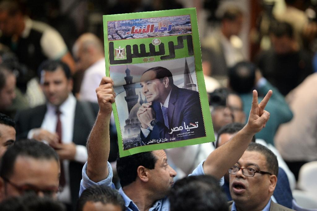 An Egyptian man carries a copy of a newspaper, bearing the portrait of Egyptian President Abdel Fattah al-Sisi, during a press conference by election authorities that announced the incumbent had won 97 percent of votes to claim a second term (AFP Photo/MOHAMED EL-SHAHED )