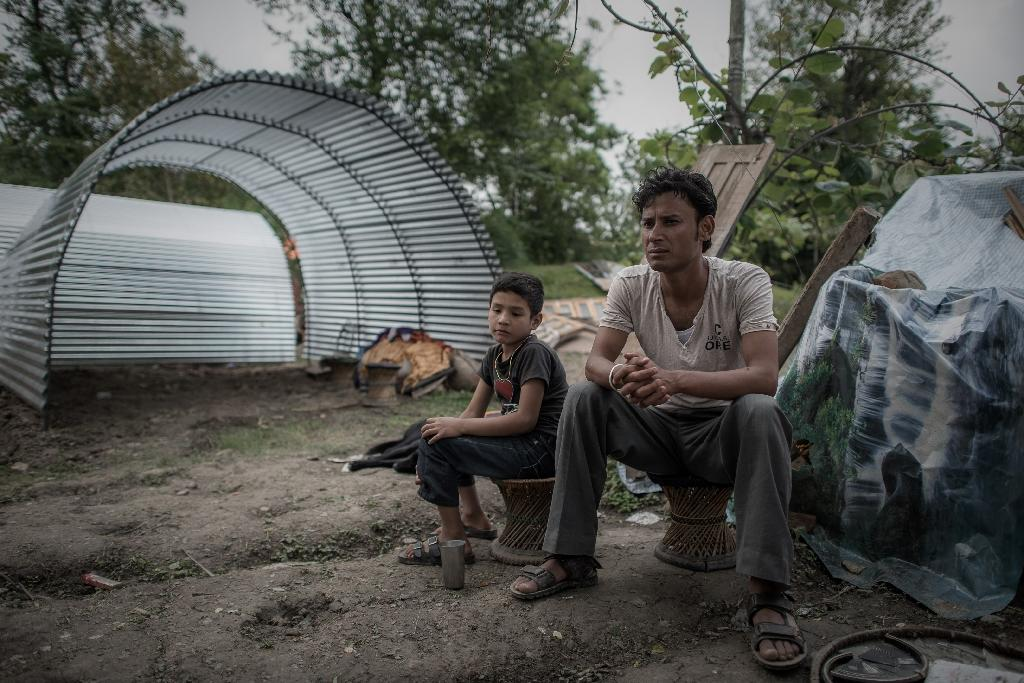 Earthquake survivor Navaraj Bista and his son sit in front of their new shelter on the outskirts of Kathmandu, following devastating 7.8 magnitude quake that hit on April 25 (AFP Photo/Philippe Lopez)