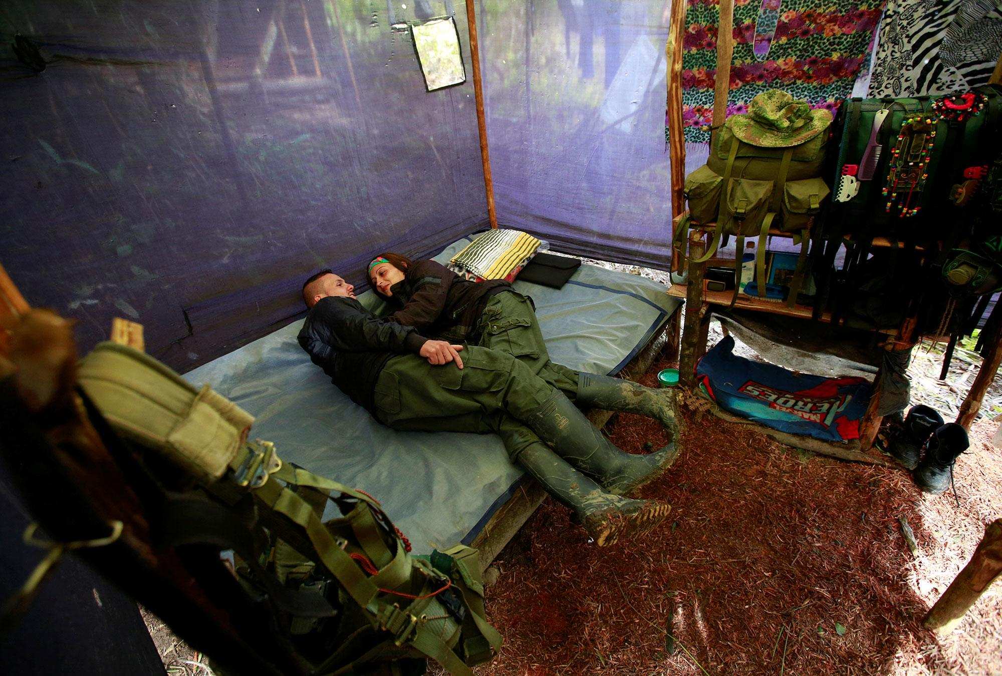 <p>A couple from the 51st Front of the Revolutionary Armed Forces of Colombia (FARC) rest inside a tent at a camp in Cordillera Oriental, Colombia, August 16, 2016. (John Vizcaino/Reuters) </p>