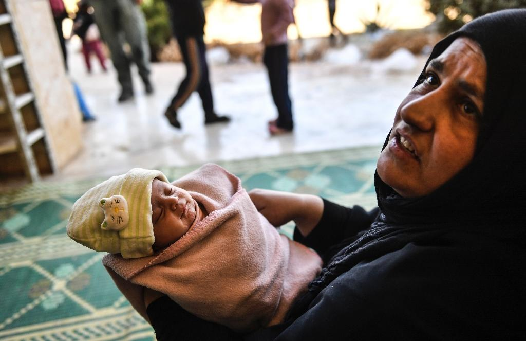 A former IS human shield holding a new-born baby after fleeing from the centre of Raqa (AFP Photo/BULENT KILIC)