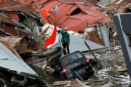 A man gestures towards a search and rescue team while looking for victims in the earthquake and liquefaction affected Balaroa neighbourhood in Palu