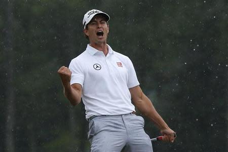Adam Scott of Australia celebrates sinking a birdie putt on the 18th green during the final round in the 2013 Masters golf tournament in Augusta