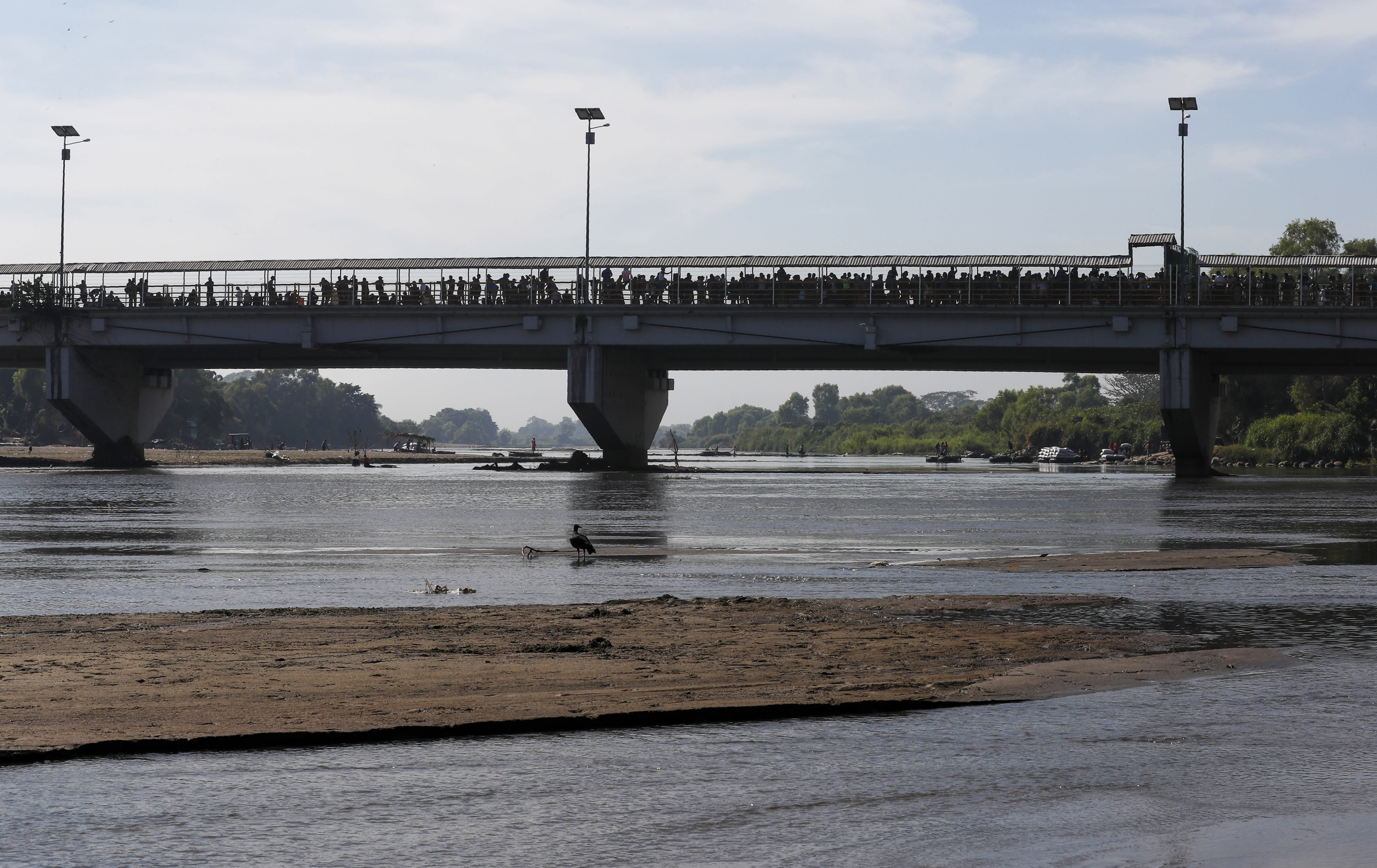 Migrants crowd the the bridge spanning the Suchiate River on the border between Guatemala and Mexico in Ciudad Hidalgo, Saturday, Jan. 18, 2020. More than a thousand Central American migrants surged onto the bridge as Mexican National Guardsmen attempted to impede their journey north. (AP Photo/Marco Ugarte)