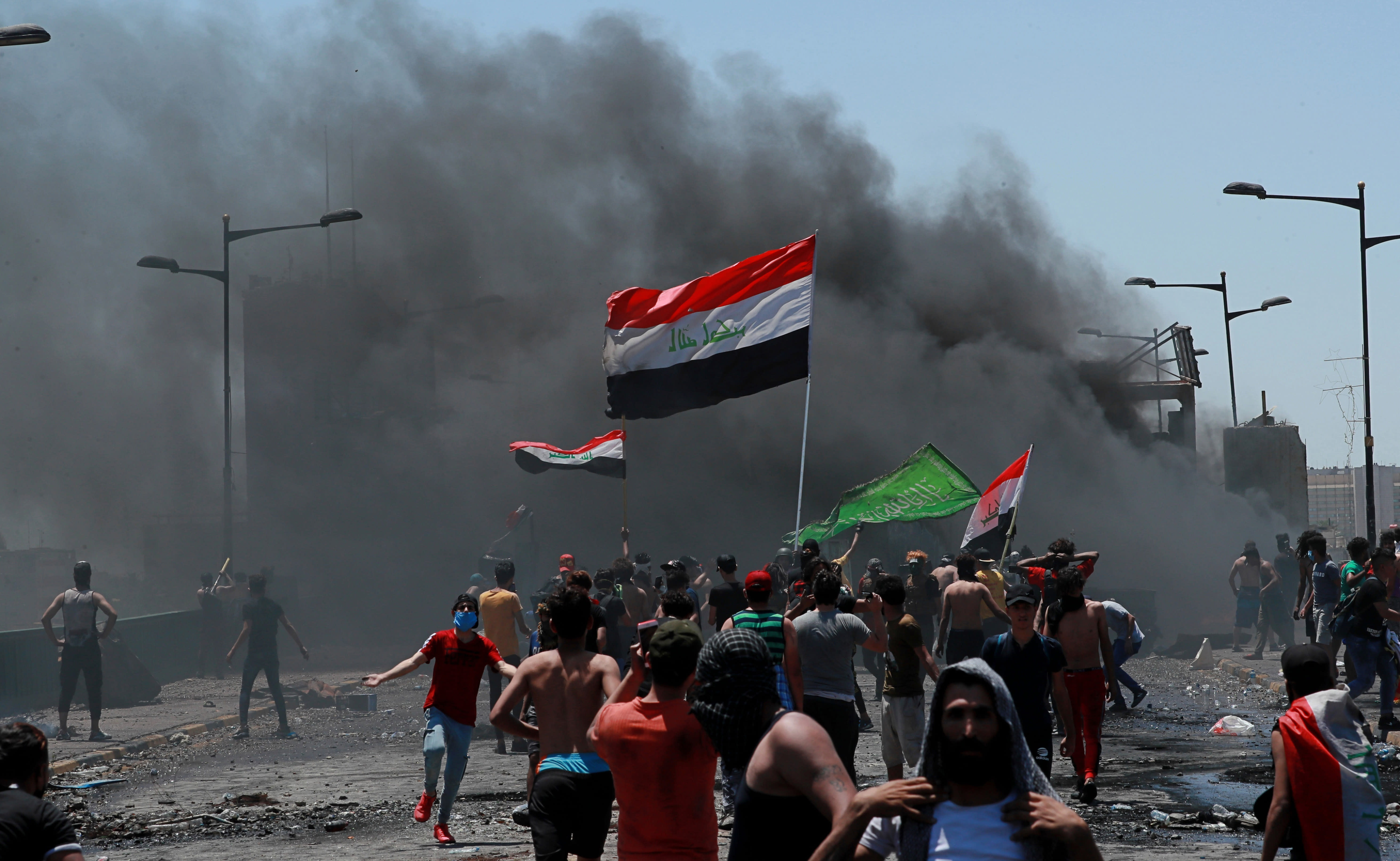 Anti-government protesters burn tires in front of barriers set up by security forces to close the Jumhuriyah Bridge leading to the Green Zone government area, during ongoing protests in Baghdad, Iraq, Sunday, May 10, 2020. Protesters were back on the streets three days after Mustafa al-Kadhimi was appointed as Iraq's new prime minister. (AP Photo/Hadi Mizban)