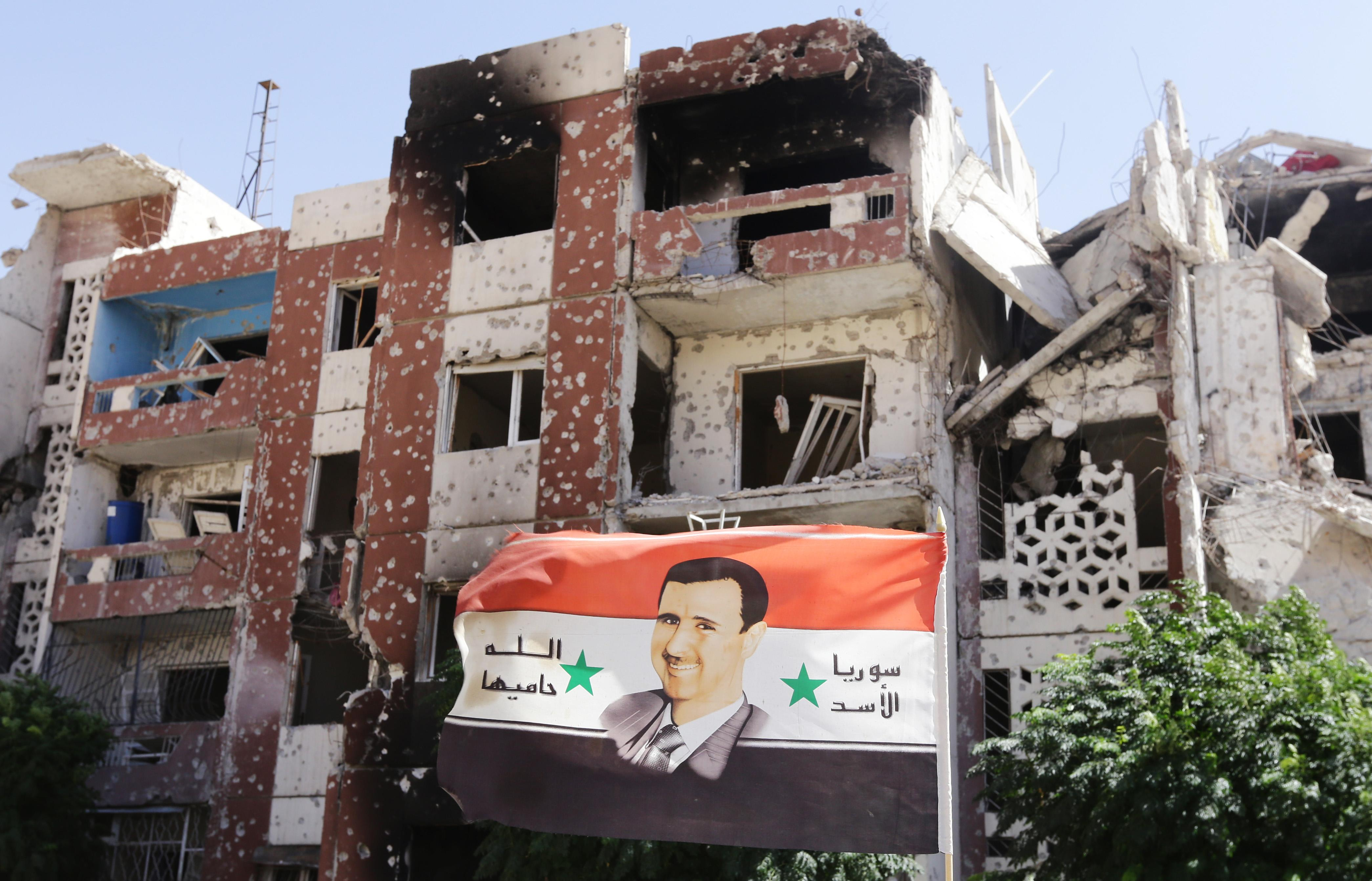 A flag showing President Bashar al-Assad flutters near damaged buildings in Adra, Syria, on September 25, 2014 (AFP Photo/Louai Beshara)