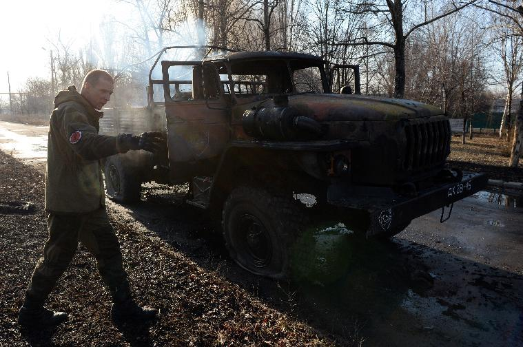 A member of a unit of the rebelian military police examines a burning military track following shelling in Donetsk, on February 13, 2015 (AFP Photo/Vasily Maximov)