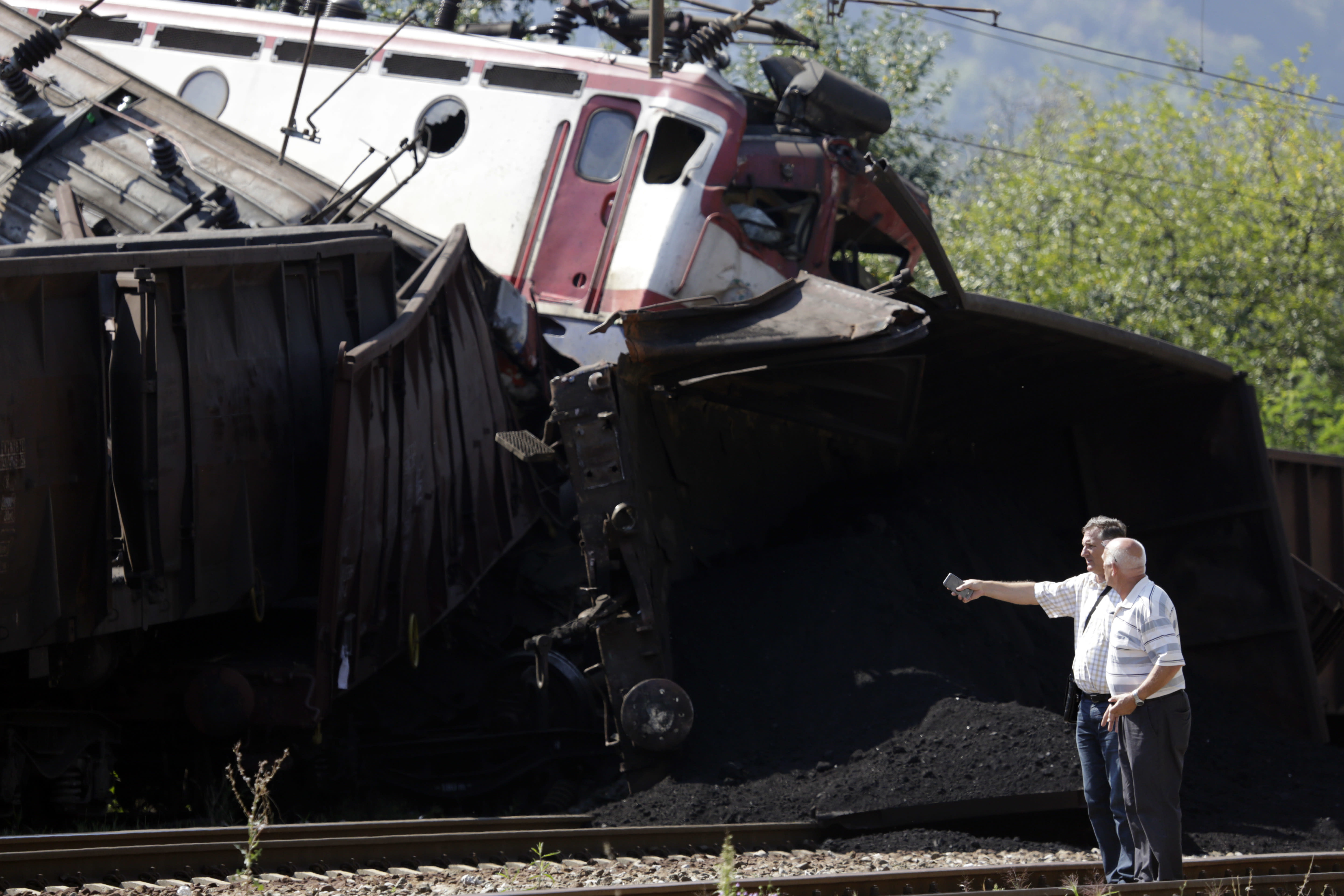 People study the scene where two cargo trains collided at the train station in Jablanica, about 80 kms south of Sarajevo, Bosnia, Thursday, Aug. 23, 2018. Police say two people have been killed and one was seriously injured in a head-on freight train collision in southern Bosnia, early Thursday. (AP Photo/Amel Emric)