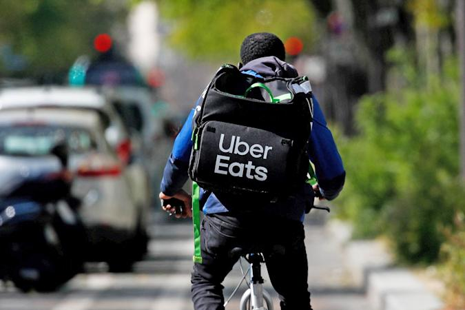 An Uber Eats delivery person rides down a path with their logo-emblazoned delivery backpack.