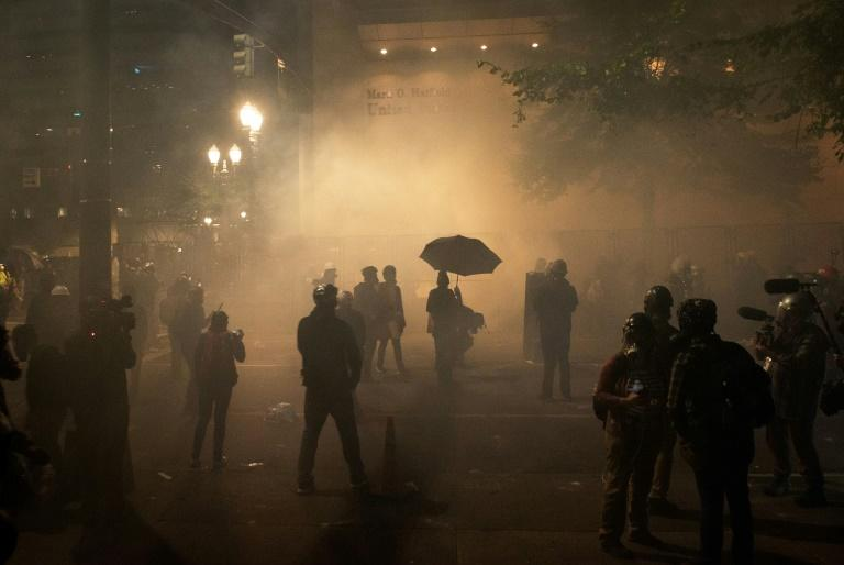 Protestors walk through a haze of tear gas near the Mark O Hatfield federal courthouse in downtown Portland, Oregon (AFP Photo/Kathryn ELSESSER)
