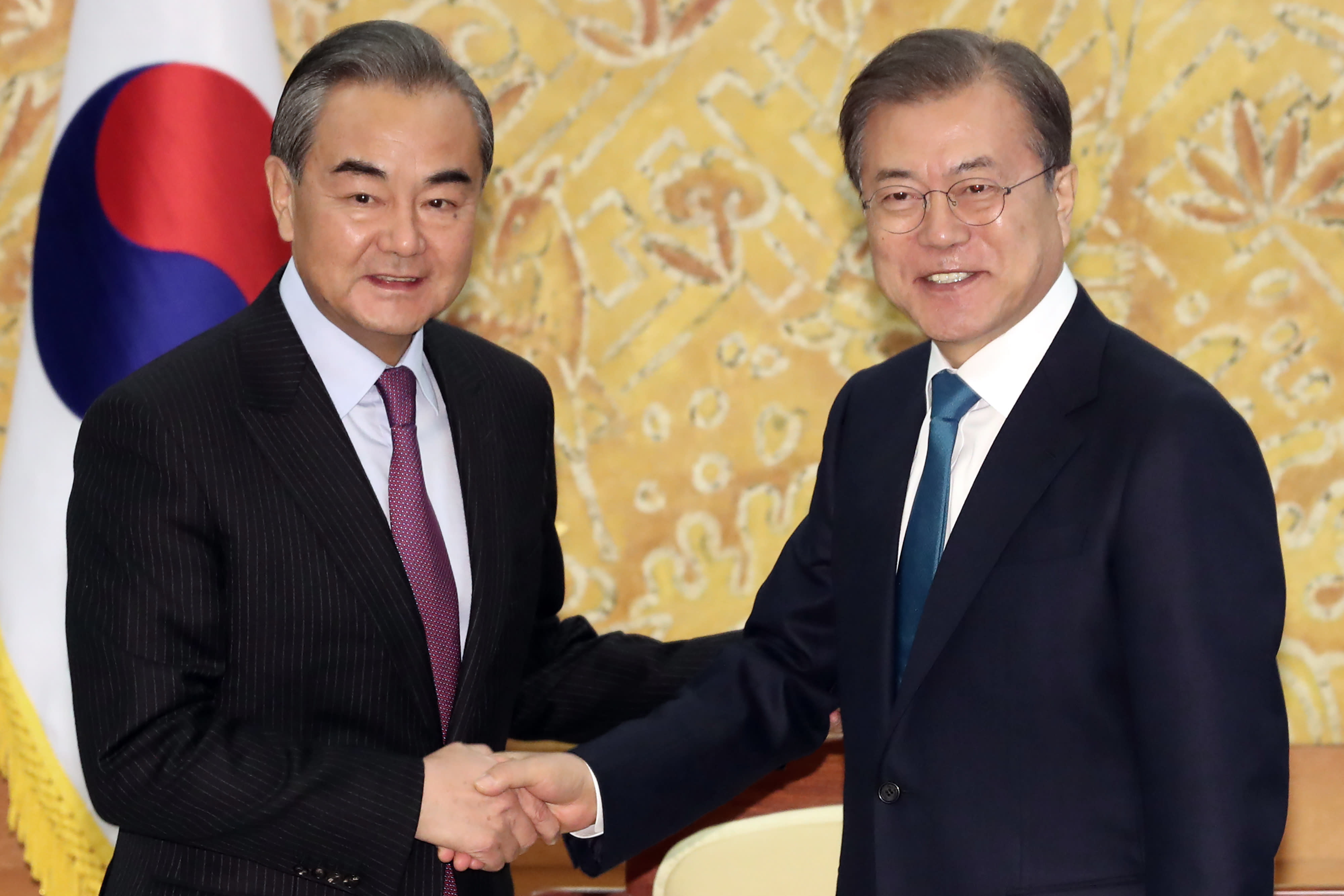 South Korean President Moon Jae-in, right, shakes hands with Chinese Foreign Minister Wang Yi during a meeting at the presidential Blue House in Seoul, South Korea, Thursday, Dec. 5, 2019. Wang arrived in South Korea on Wednesday for his first visit in four years amid efforts to patch up relations damaged by Seoul's decision to host a U.S. anti-missile system that Beijing perceives as a security threat. (Lee Jin-wook/Yonhap via AP)