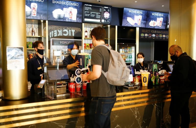 """People purchase refreshments inside the foyer of the Odeon Luxe Leicester Square cinema, on the opening day of the film """"Tenet"""", in London"""