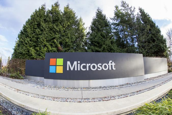 Redmond, WA, USA - January 30, 2018: One of the biggest Microsoft signs is placed next to green trees at a public intersection near Microsoft's Redmond campus