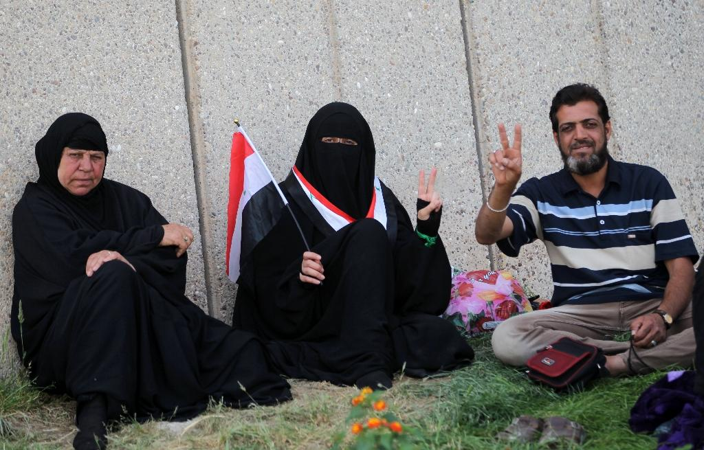 Iraqis pose in the parade grounds outside the parliament in Baghdad's heavily fortified Green Zone on May 1, 2016, the day after supporters of Shiite cleric Moqtada al-Sadr broke into the area (AFP Photo/Ahmad Al-Rubaye)