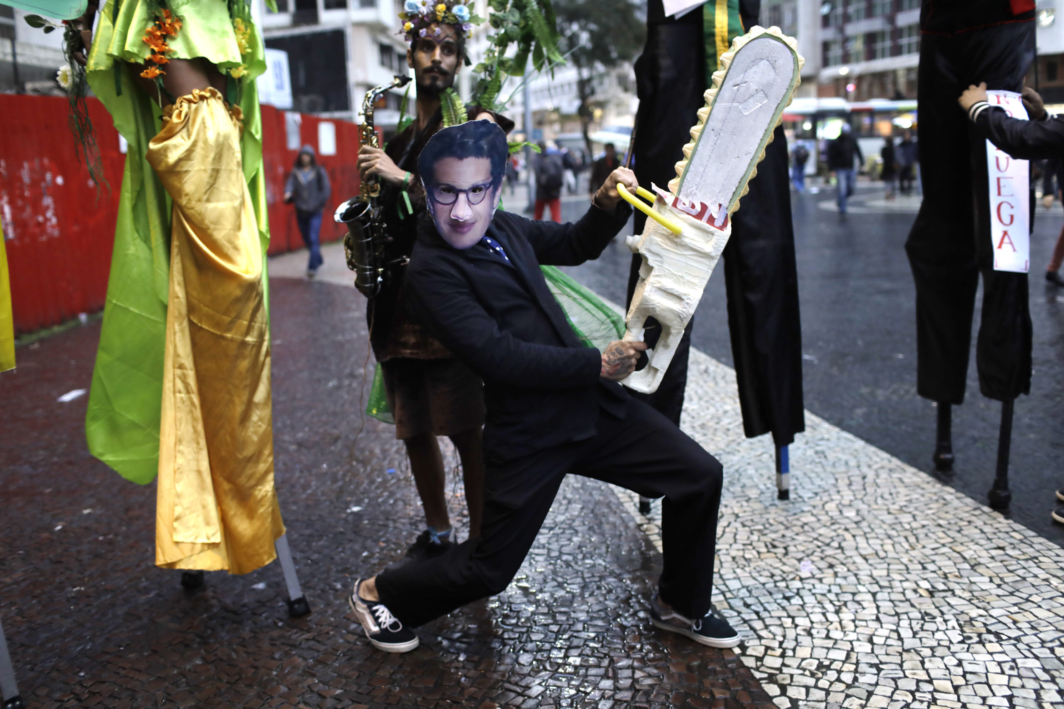 A demonstrator wearing a mask with the likeness of Brazil's Environment Minister Ricardo Salles brandishing a fake chainsaw, participates in a protest to defend of the Amazon, in Rio de Janeiro, Brazil, Thursday, Sept. 5, 2019. The Brazilian Amazon saw almost 31 thousand fires in August, the highest for the month since 2010, according to Brazil's National Institute for Space Research. (AP Photo/Silvia Izquierdo)