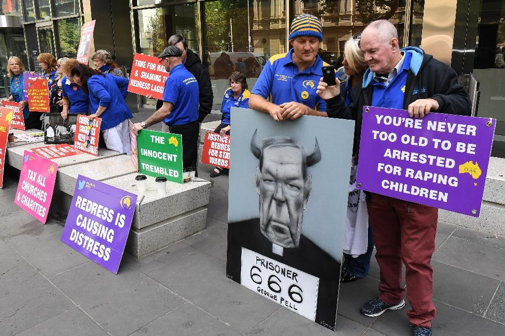 Protesters hold placards outside the court ahead of the sentencing of Cardinal George Pell in Melbourne on Wednesday