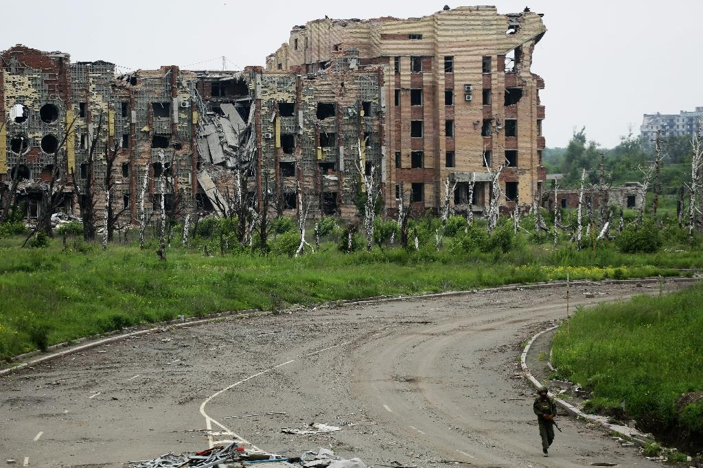 An armed pro-Russian separatist of the self-proclaimed Donetsk People's Republic walks in front of the destroyed Donetsk International Airport on June 1, 2016 (AFP Photo/Aleksey Filippov)