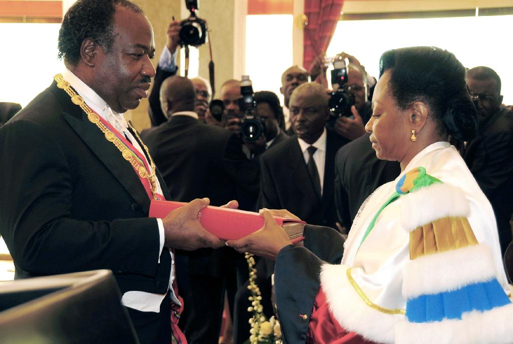 Gabon Constitutional Court President Marie Madeleine Mborantsuo hands the constitution to Ali Bongo after he was sworn in as president in October, 2009 in Libreville (AFP Photo/Wils Yanick Maniengue)