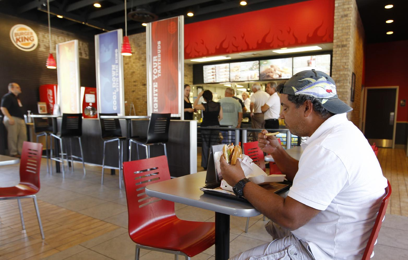 In this March 28, 2012 photo, Norman Garcia eats a burger and fries at a Burger King restaurant in Miami. Burger King launches 10 menu items including smoothies, frappes, specialty salads and snack wraps in a star-studded TV ad campaign. It's the biggest menu expansion since the chain opened its doors in 1954. (AP Photo/Luis M. Alvarez)