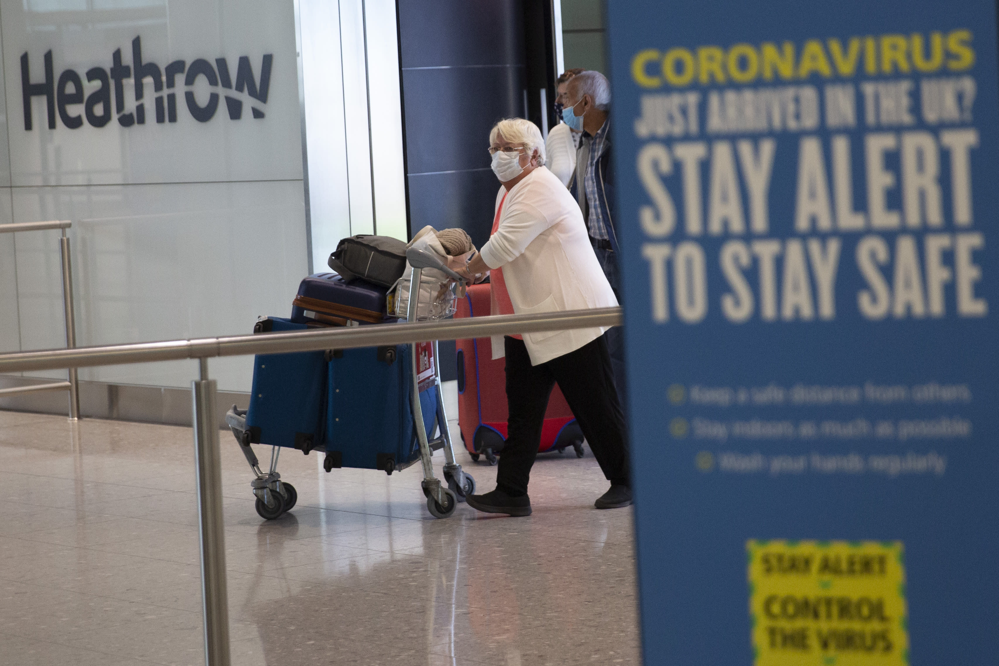 Passengers wearing face masks arrive at Heathrow Airport on the first day of new rules that require people arriving in Britain from overseas to quarantine themselves for 14 days. (AP)
