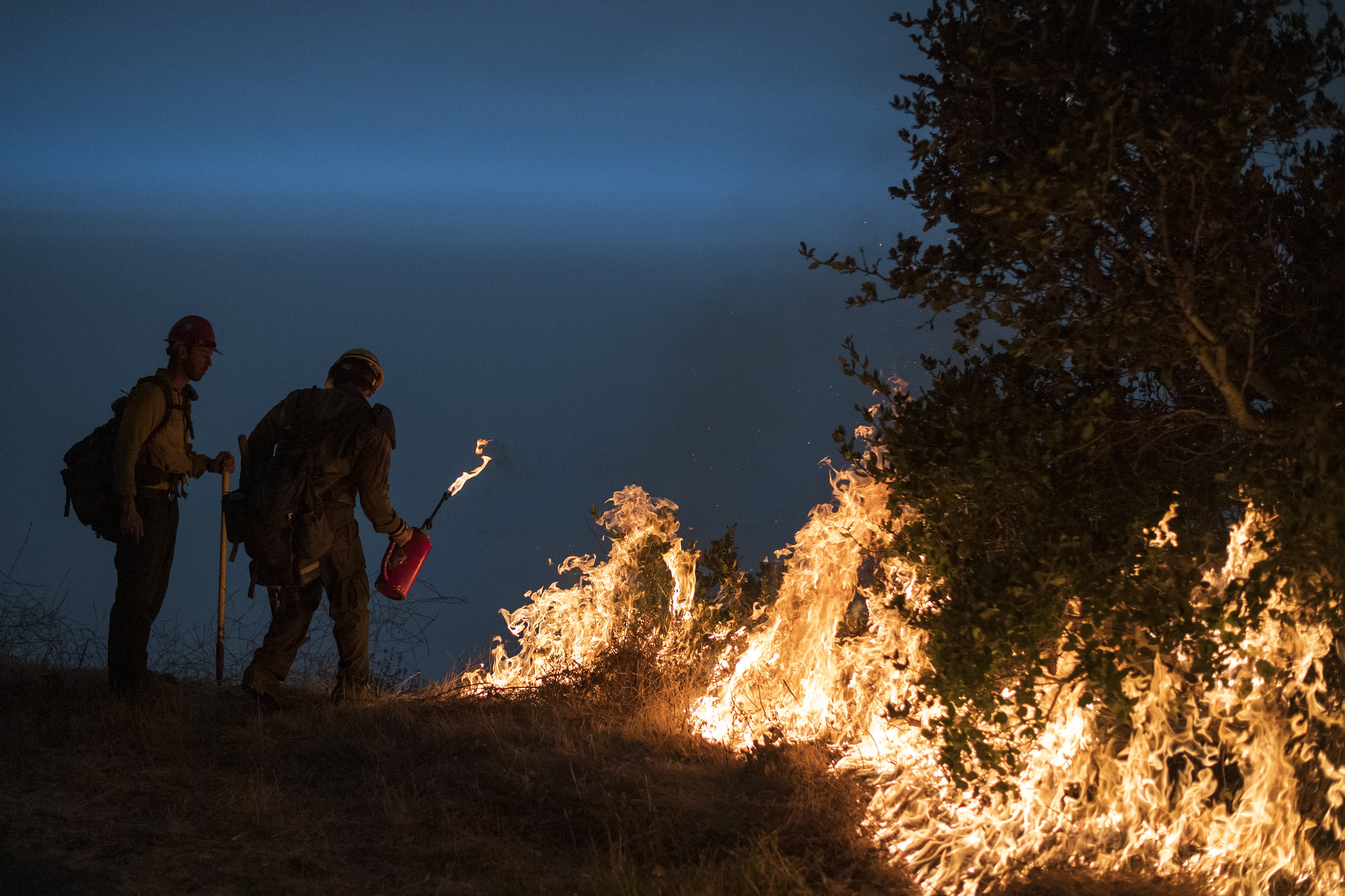 FILE - In this Sept. 11, 2020, file photo, firefighters light a controlled burn along Nacimiento-Fergusson Road to help contain the Dolan Fire near Big Sur, Calif. Rain showers fell Thursday, Sept. 24, 2020, on the northwestern edges of fire-ravaged California but forecasters warned residents to not be fooled: a new round of hot, dry and windy weather is expected by the weekend. (AP Photo/Nic Coury, File)