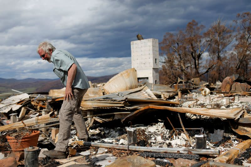 Donald Graham, 68, looks through the remains of his home which was destroyed by bushfires in Buchan, Victoria, Australia