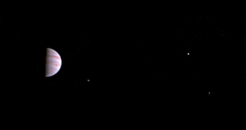 Image taken from NASA's Juno spacecraft shows Jupiter and three of it's four largest moons (L-R) Io, Europa and Ganymede (AFP Photo/)