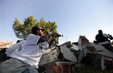 A vigilante member of the community police aims his weapon after entering the village of Paracuaro in Michoacan state, January 4, 2014. REUTERS/Jorge Dan Lopez/Files