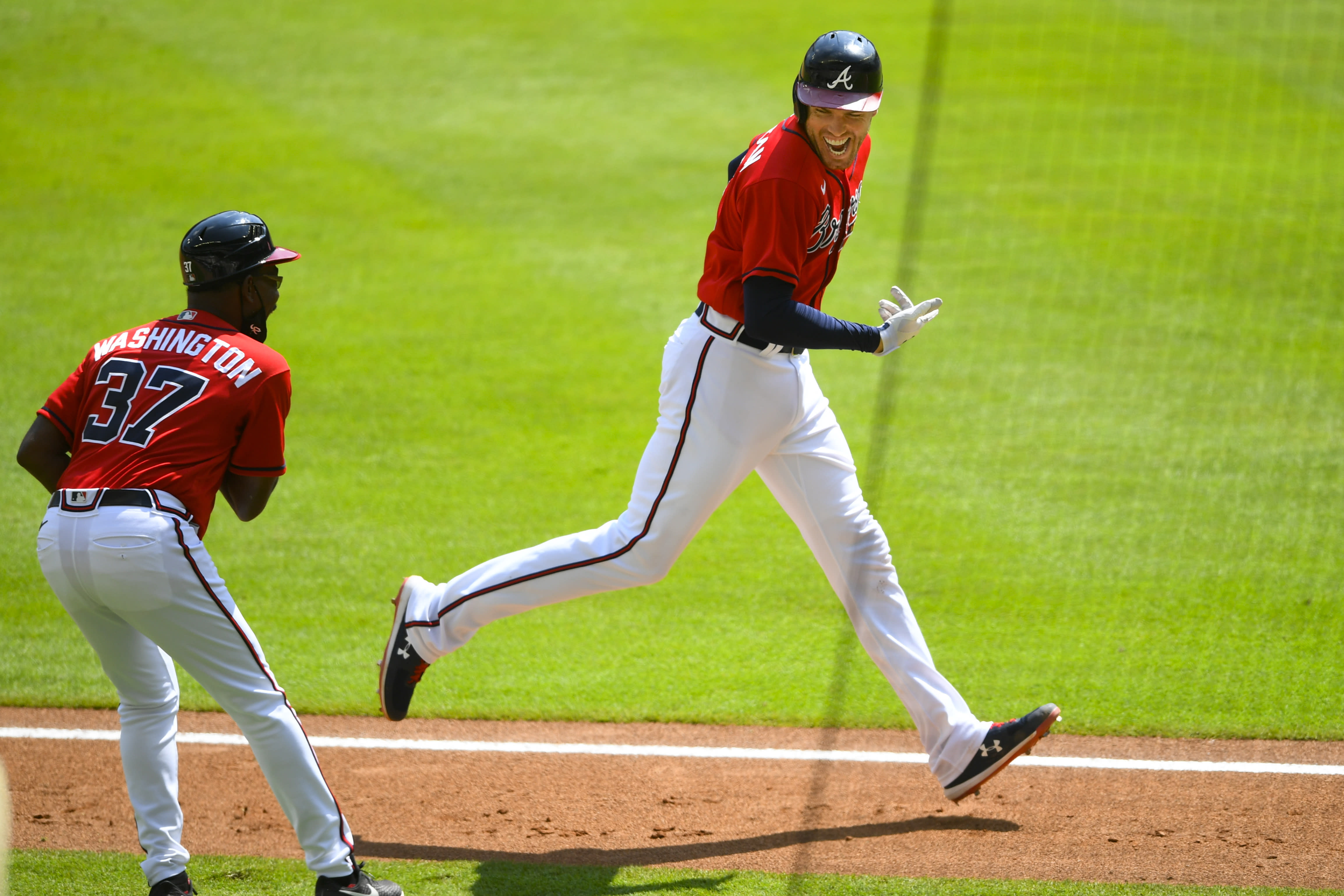 Atlanta Braves' Freddie Freeman reacts as he passes coach Ron Washington (37) after rounding third base during his grand slam home run in the sixth inning of a baseball game against the Washington Nationals, Sunday, Sept. 6, 2020, in Atlanta. (AP Photo/John Amis)