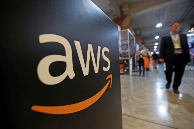 A man walks past an Amazon AWS sign with logo.
