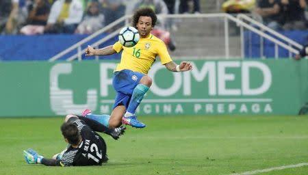El brasileño Marcelo (16) deja atrás al arquero de Paraguay, Antony Silva, durante un partido disputado en el Arena Corinthians, Sao Paulo, Brasil