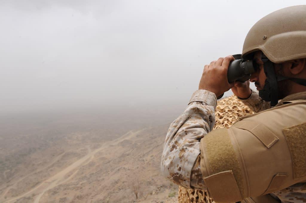 A Saudi soldier looks through binoculars from a position on the Saudi-Yemeni border, in southwestern Saudi Arabia, on April 13, 2015