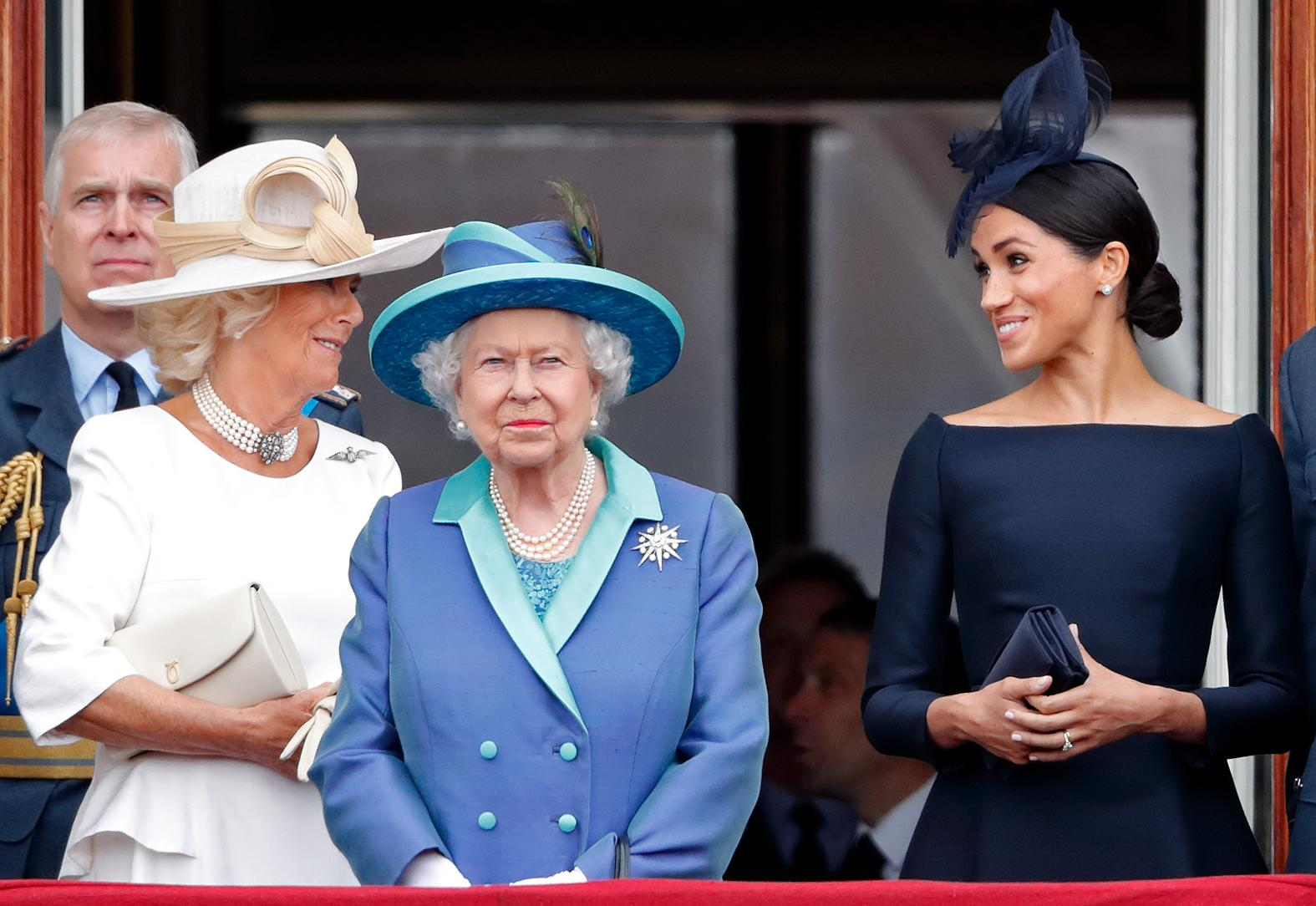 LONDON, UNITED KINGDOM - JULY 10: (EMBARGOED FOR PUBLICATION IN UK NEWSPAPERS UNTIL 24 HOURS AFTER CREATE DATE AND TIME) Camilla, Duchess of Cornwall, Queen Elizabeth II and Meghan, Duchess of Sussex watch a flypast to mark the centenary of the Royal Air Force from the balcony of Buckingham Palace on July 10, 2018 in London, England. The 100th birthday of the RAF, which was founded on on 1 April 1918, was marked with a centenary parade with the presentation of a new Queen's Colour and flypast of 100 aircraft over Buckingham Palace. (Photo by Max Mumby/Indigo/Getty Images)