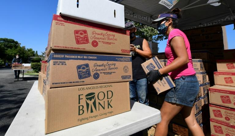 Volunteers prepare to load vehicles with boxes of food at a food bank in Duarte, California on July 8, 2020