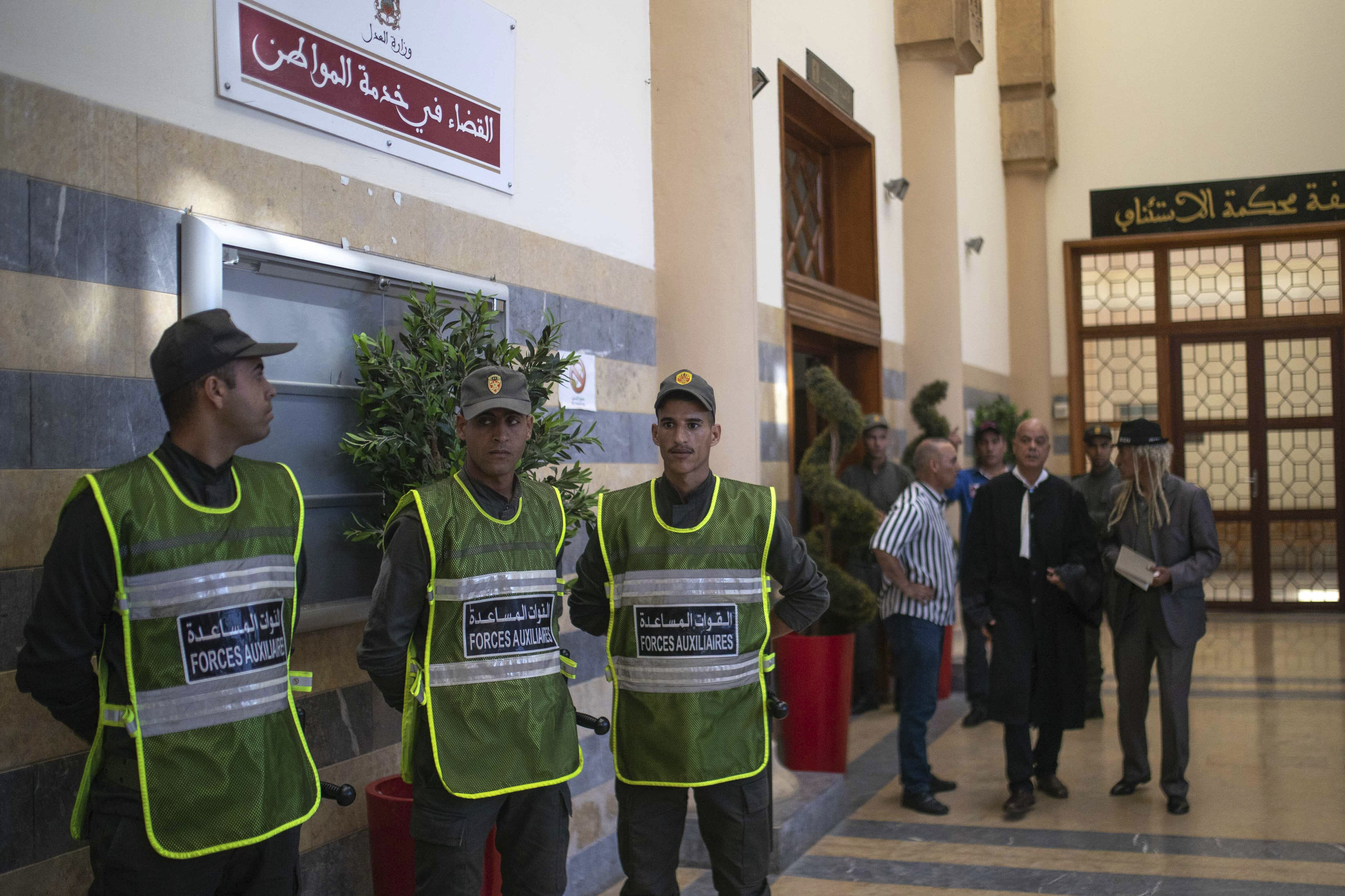 Security forces stand guard outside a court room before the start of a final trial session for suspects charged in connection with killing of two Scandinavian tourists in Morocco's Atlas Mountains, in Sale, near Rabat, Morocco, Thursday, July 18, 2019. The three main defendants in the brutal slaying of two female Scandinavian hikers have asked for forgiveness from Allah ahead of a verdict. (AP Photo/Mosa'ab Elshamy)