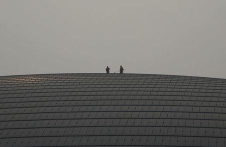Workers clean the roof of National Grand Theatre on a polluted day in Beijing, China, February 15, 2017. REUTERS/Jason Lee