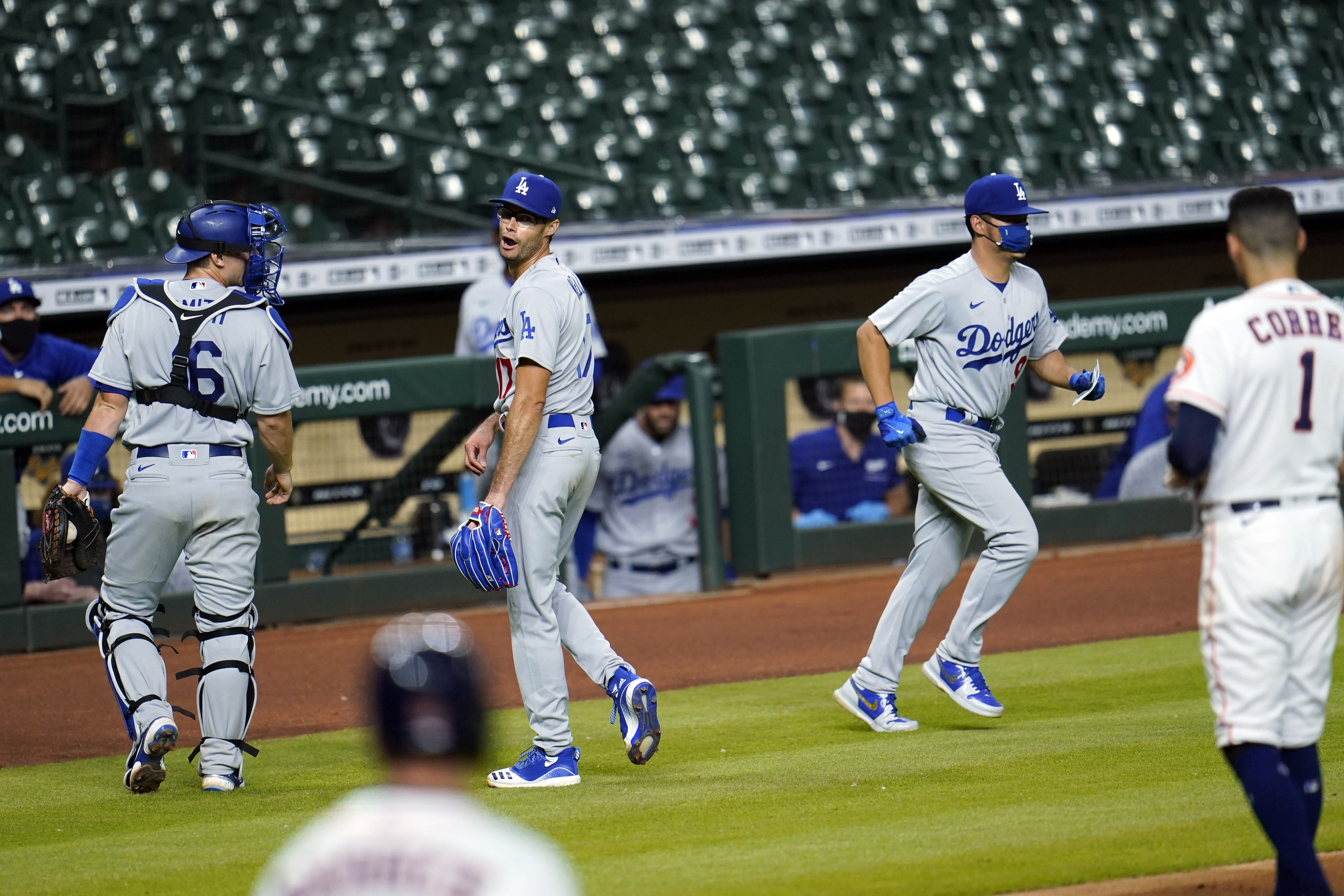 Los Angeles Dodgers relief pitcher Joe Kelly, second from left, talks back to Houston Astros' Carlos Correa (1) after the sixth inning of a baseball game Tuesday, July 28, 2020, in Houston. Both benches emptied onto the field during the exchange. (AP Photo/David J. Phillip)