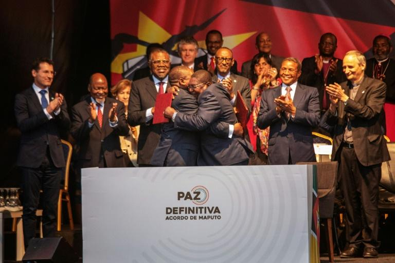 Mozambique's President Filipe Nyusi and Renamo leader Ossufo Momade hug after signing the landmark peace agreement on August 6 (AFP Photo/STRINGER)