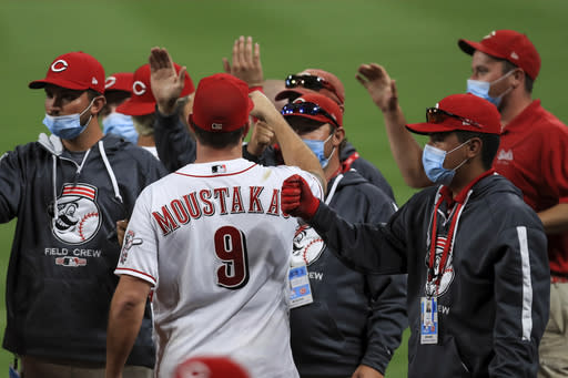 Cincinnati Reds' Mike Moustakas fist bumps members of the Reds' grounds crew after a baseball game against the Milwaukee Brewers in Cincinnati, Wednesday, Sept. 23, 2020. The Reds won 6-1. (AP Photo/Aaron Doster)