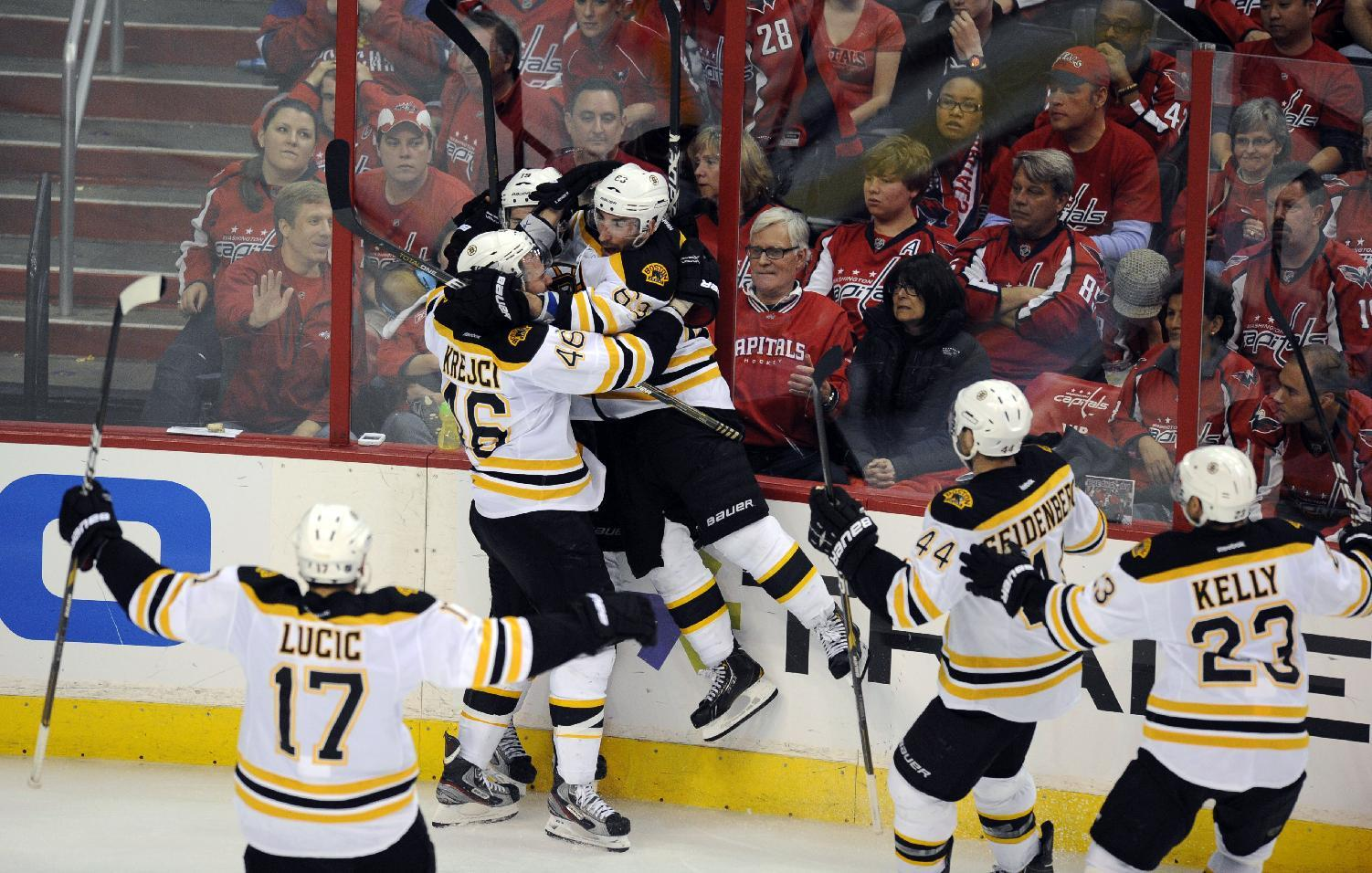 Members of the Boston Bruins including Brad Marchand (63), David Krejci (46), Milan Lucic (17), Dennis Seidenberg (44), of Germany, and Boston Bruins center Chris Kelly (23) celebrate with Tyler Seguin, top left, after Seguin scored the game-winning goal to beat the Washington Capitals 4-3 in overtime in Game 6 of an NHL hockey Stanley Cup first-round playoff series, Sunday, April 22, 2012, in Washington. (AP Photo/Nick Wass)