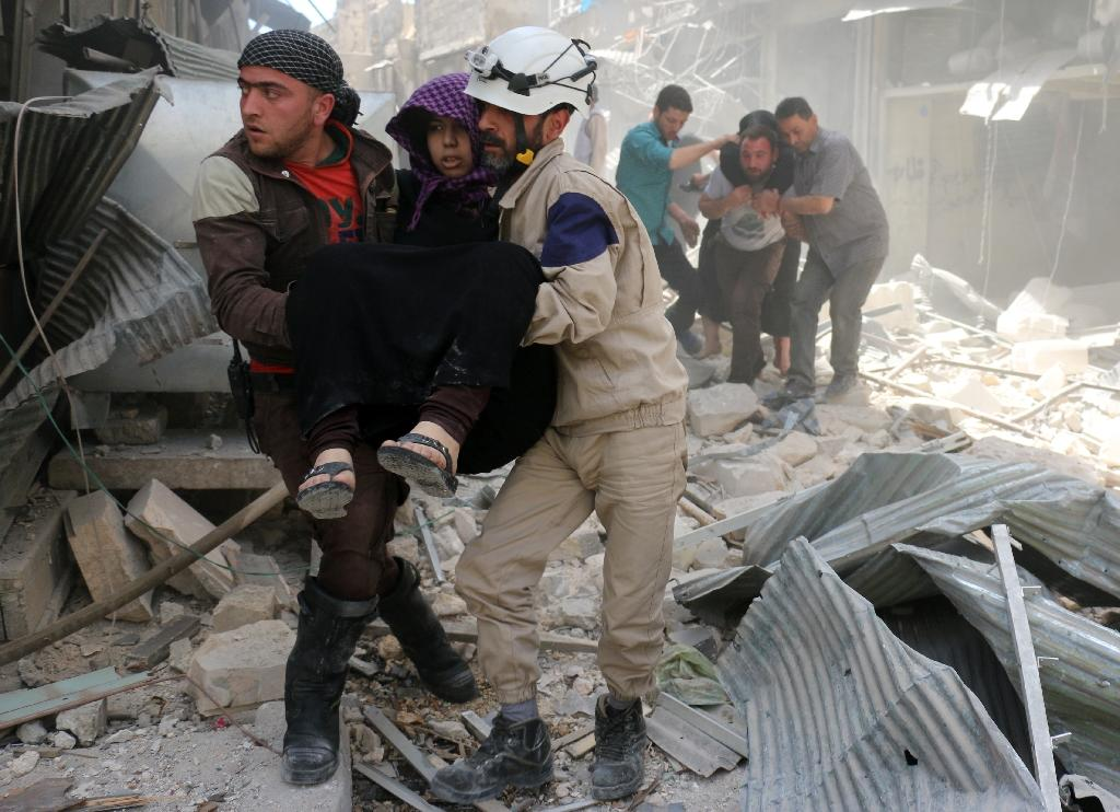 Civil defence volunteers evacuate wounded people following a reported airstrike in the rebel-held neighbourhood of Hayy Aqyul, in Syria's second city Aleppo, on April 22, 2016 (AFP Photo/Ameer Alhalbi)