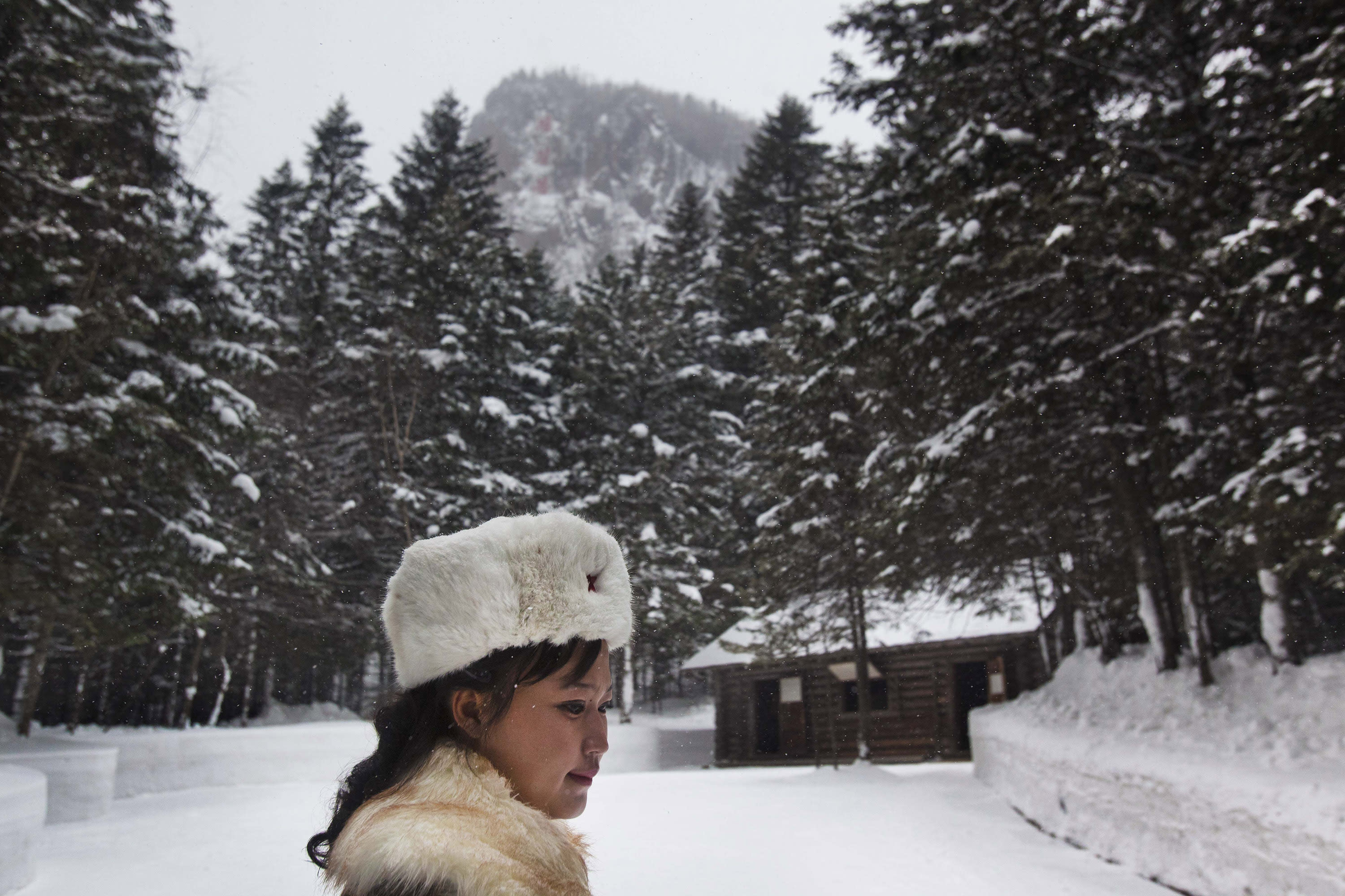 In this Monday, April 2, 2012 photo, a North Korean soldier, working as a guide, walks near a cabin that is said to have been the home of the late North Korean leader Kim Il Sung and the birthplace of his son and late leader Kim Jong Il at what was a secret military camp during the fight against the Japanese at the foot of Mount Paektu, North Korea. (AP Photo/David Guttenfelder)