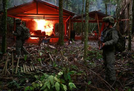 A Colombian anti-narcotics policeman stands guard after burning a cocaine lab, which police said belongs to criminal gangs, in a rural area of Calamar in Guaviare state, Colombia, August 2, 2016. REUTERS/John Vizcaino