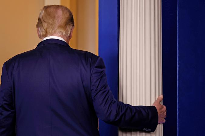 A photo of the back of donald trump who's holding onto a pillar with his right hand.