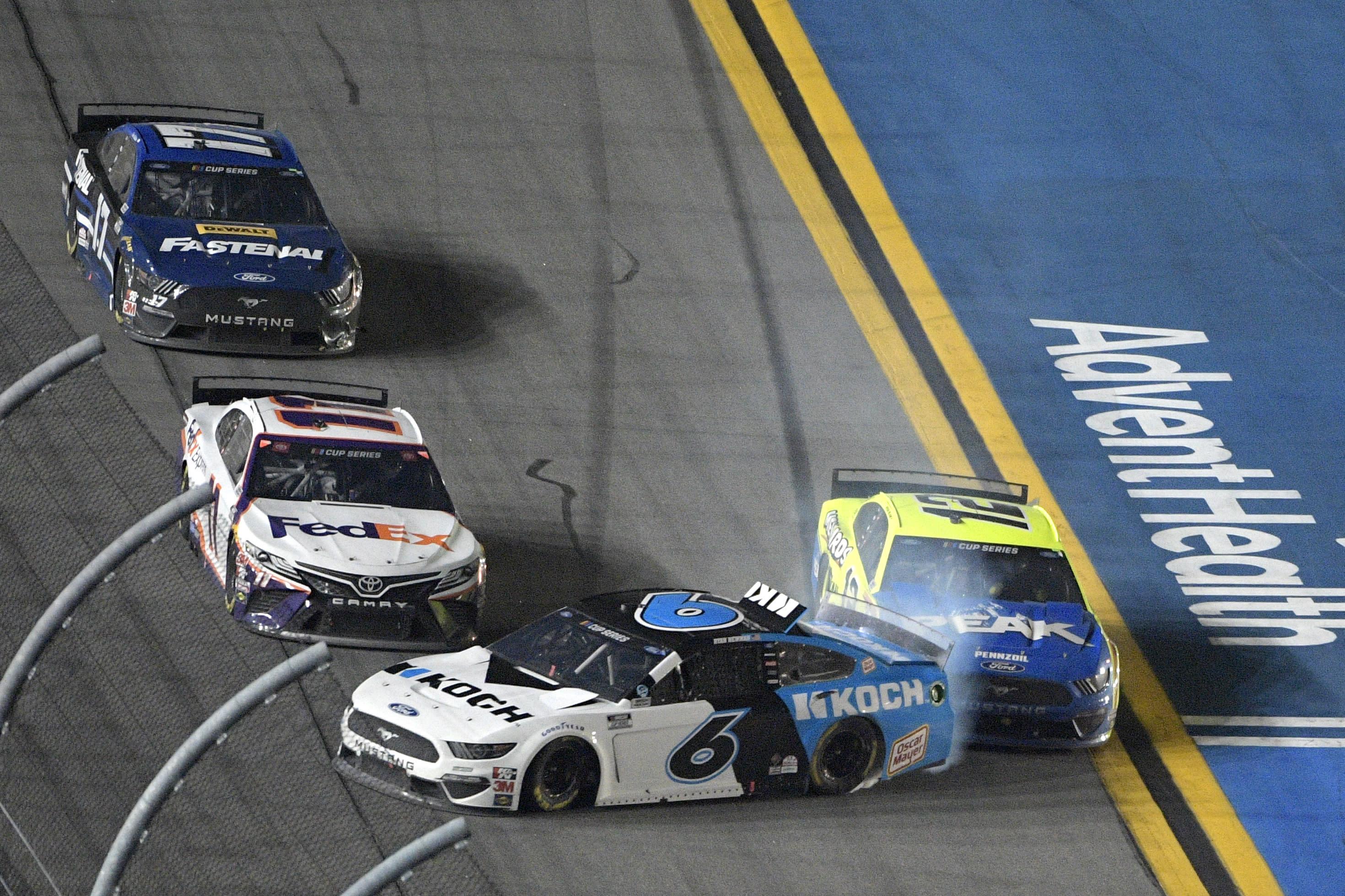 Ryan Newman (6) gets turned into the wall by Ryan Blaney (12) as Denny Hamlin (11) misses them along the front stretch to win the NASCAR Daytona 500 auto race at Daytona International Speedway, Monday, Feb. 17, 2020, in Daytona Beach, Fla. (AP Photo/Phelan M. Ebenhack)
