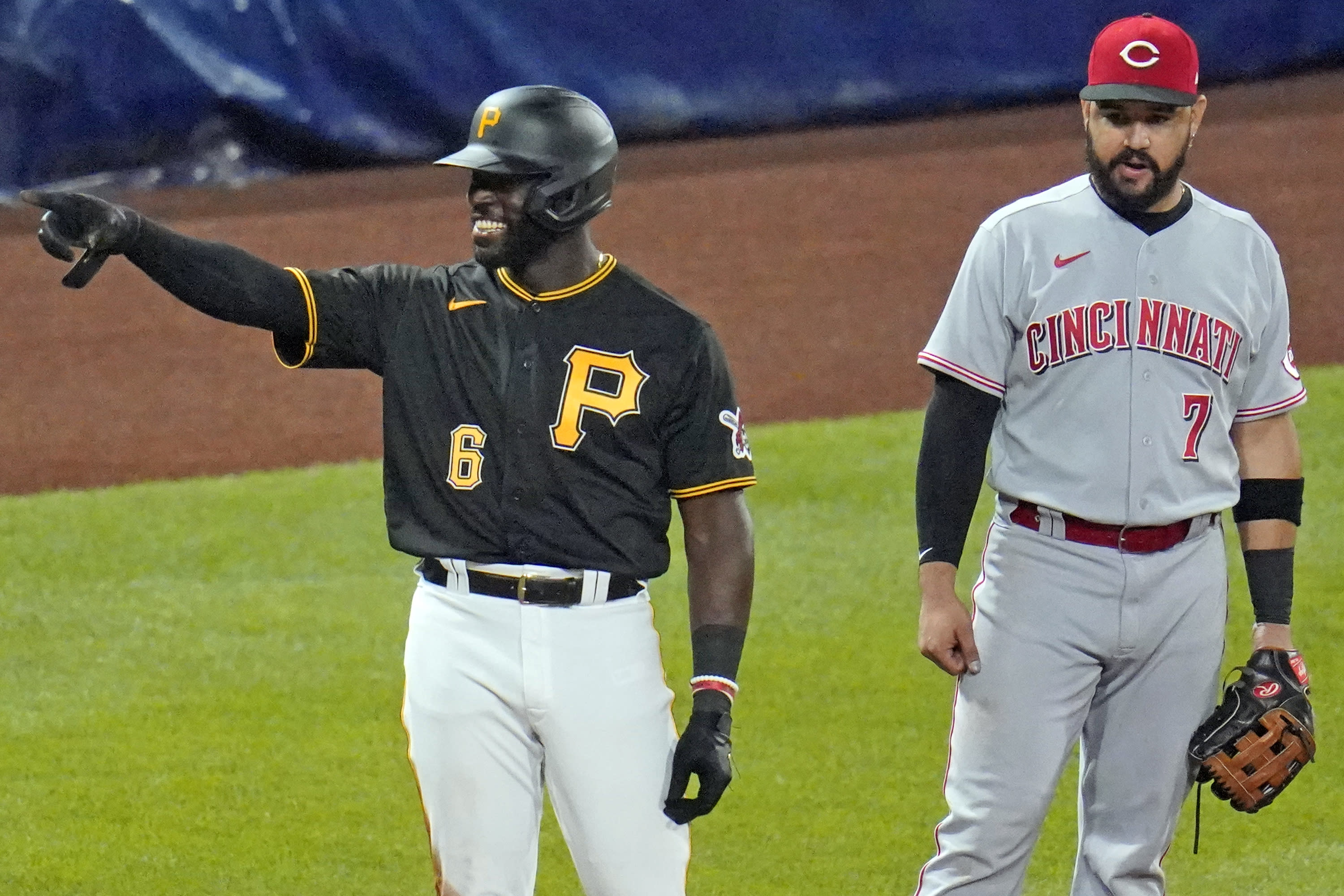 CORRECTS THAT ALFORD DROVE IN TWO RUNS, INSTEAD OF ONE - Pittsburgh Pirates' Anthony Alford (6) celebrates as he stands on third base in front of Cincinnati Reds third baseman Eugenio Suarez (7) after driving in two runs with a triple off starting pitcher Trevor Bauer during the fourth inning of the second baseball game of a doubleheader in Pittsburgh, Friday, Sept. 4, 2020. (AP Photo/Gene J. Puskar)