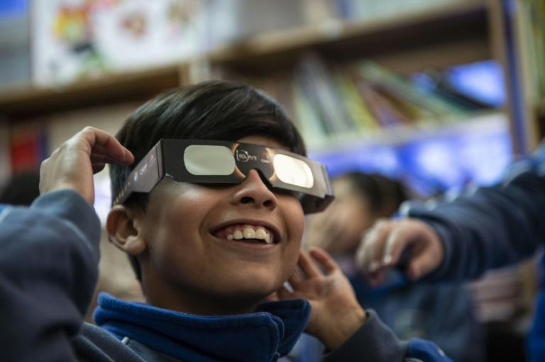 A schoolboy tries on special sunglasses at the Pedro Pablo Munoz school in La Higuera, Coquimbo Region, Chile, on the eve of a solar eclipse (AFP Photo/Martin BERNETTI)