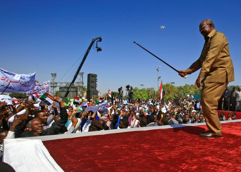 Bashir performs with his cane as he addresses a rally of his supporters in the capital Khartoum in January last year (AFP Photo/ASHRAF SHAZLY)