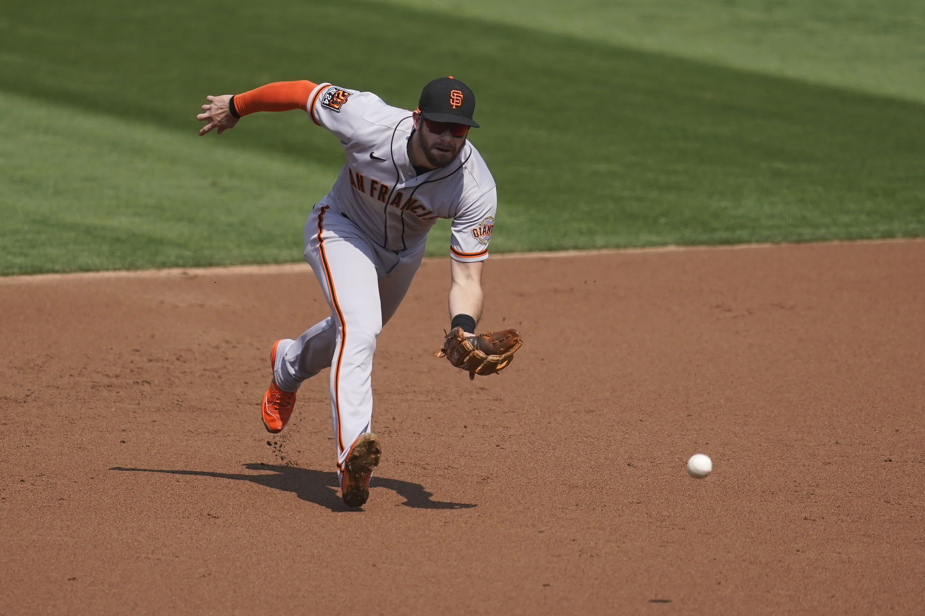 San Francisco Giants third baseman Evan Longoria fields Oakland Athletics' Mark Canha's groundout during the first inning of a baseball game in Oakland, Calif., Sunday, Sept. 20, 2020. (AP Photo/Jeff Chiu)
