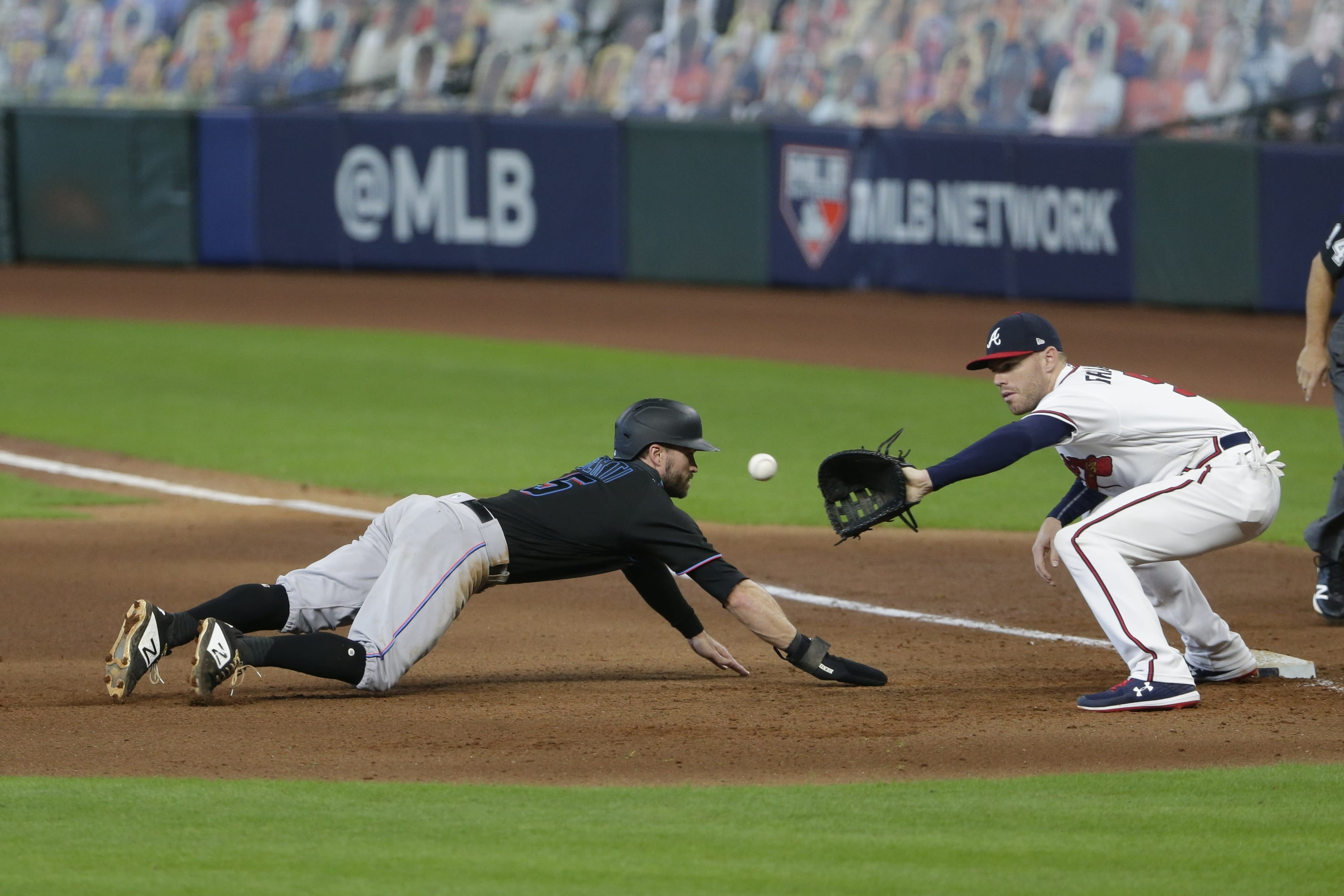 Miami Marlins' Jon Berti dives back to first base as Atlanta Braves first baseman Freddie Freeman attempt to tag him out during the eighth inning in Game 2 of a baseball National League Division Series Wednesday, Oct. 7, 2020, in Houston. (AP Photo/Michael Wyke)